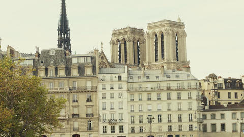 Spire of the famous Notre-Dame Cathedral and old residential houses in Paris Footage