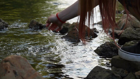 Girl touches water in a river with her hand Archivo