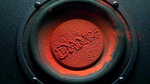 Dance caption on orange powder over trembling speaker Live Action