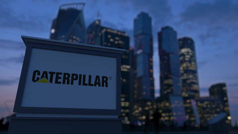 Street signage board with Caterpillar Inc. logo in the evening. Blurred busines Footage