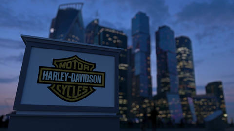 Street signage board with Harley-Davidson, Inc. logo in the evening. Blurre Footage