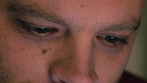 Eyes of serious caucasian man using his tablet computer. Screen reflecting in Footage