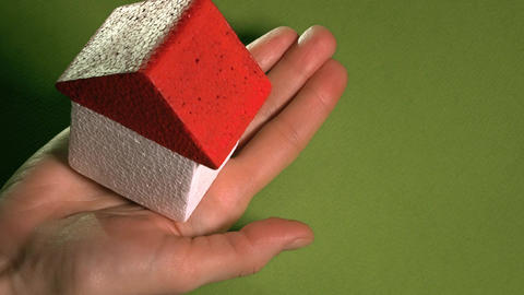 Woman holding toy house with red roof against green background. Real estate Footage