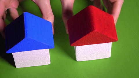 Woman realtor placing toy houses with red and blur roofs against green Footage