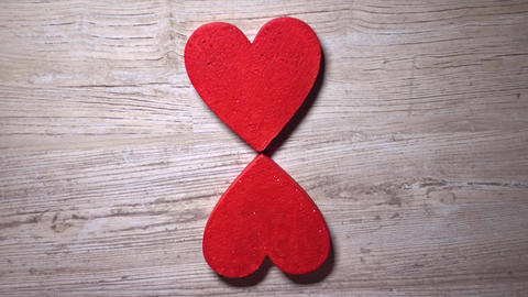 Girl placing four red hearts on a wooden table, top view. Flower, care, love Footage