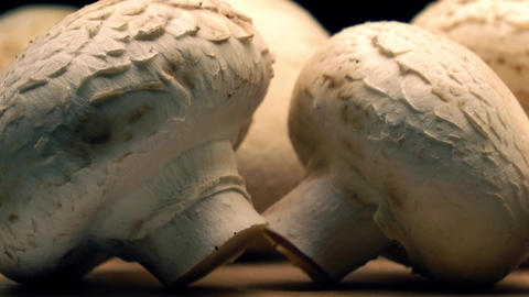 Uncooked mushrooms on wooden cutting board. 4K long pan shot Filmmaterial