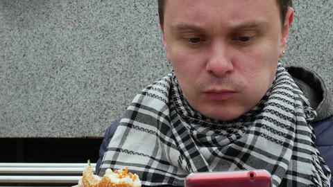 Man eating sandwich and using smart phone Footage