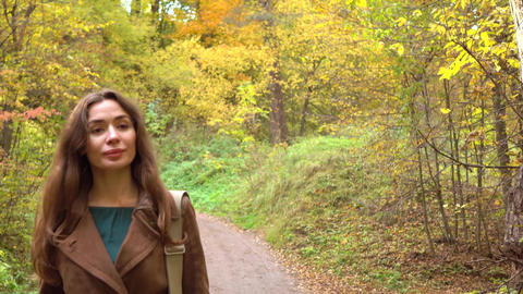 Beautiful happy brunette girl walking through autumn woods. Closeup, 4K Footage