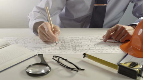 Architect or engineer using pencil working on blueprint, architectural concept Footage