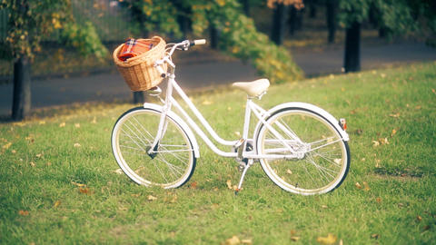 Vintage bicycle with a basket and a man riding the classic bike for a picnic in Footage