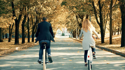 Unrecognizable couple riding the vintage classic bicycles in autumn city park Footage