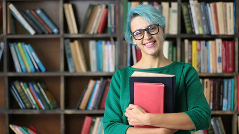 Smiling female student holding books and smiling Live Action