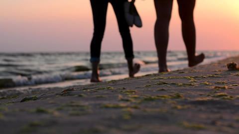 Girls walking on the beach barefoot at sunset Footage
