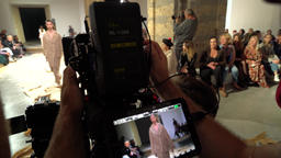 Filming of fashion show. The cameraman with the camera takes the catwalk Footage