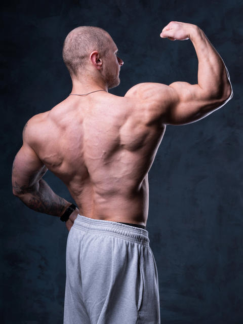 Man bodybuilder demonstrates muscles Photo