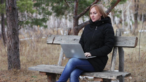 girl with a laptop on a bench in the woods. works in the open air. autumn forest Footage