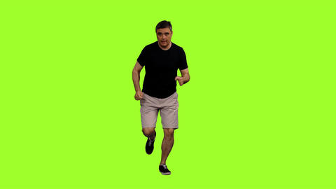 Front view of adult man in shorts and black t shirt jogging on green background Footage