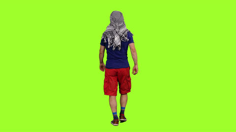Back view of male tourist in arabic scarf walks on green screen background Footage