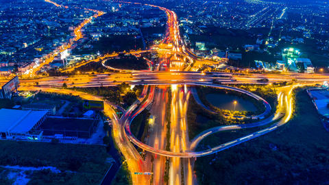 Timelapse aerial view of cityscape and traffic on highway at night Footage