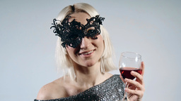 Woman in carnival mask inviting to drink wine Footage