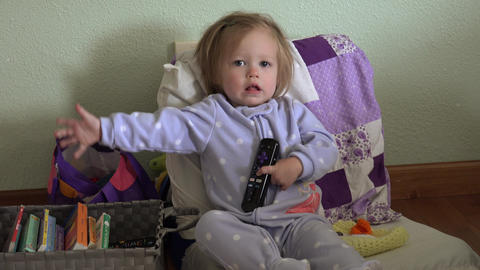 Baby blue pajamas holding tv remote controller seated with books Footage
