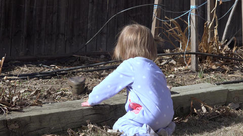 Baby kneeling outside sunny playing with garden backyard rocks Footage