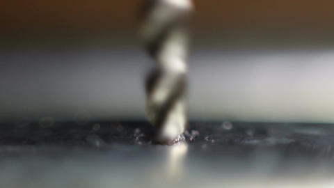 The drill bit is drilling a hole in metal Live Action