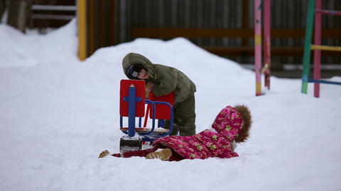 A girl and a boy are playing outside in winter Footage
