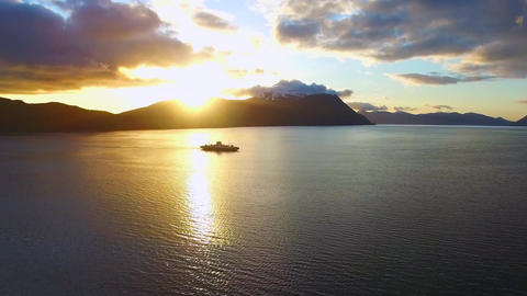 The sunset overlooking mountains and a sailing ship. Aerial view Footage