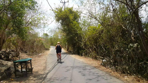 Blond european woman cycling on Lembongan island Live Action