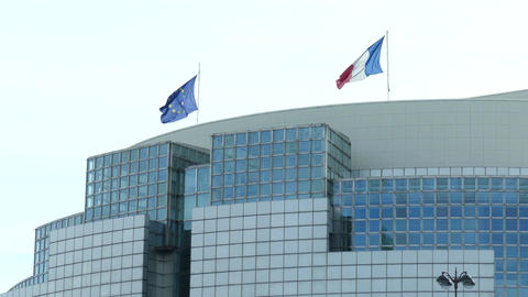 Waving flags of France and the European Union on the roof of a modern building Footage