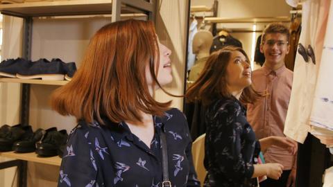 Beautiful Joyful Girl Takes Fast Fashionable Blouse from Rack Footage