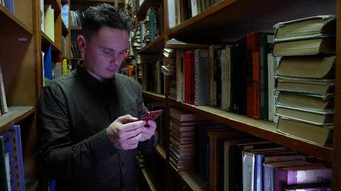 Student in the library using cellphone, browsing, reading. Bookcase bookshelves Footage