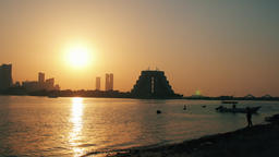 Sunset Over Manama from Muharraq coast Skyline of the city and boats in the sea Footage