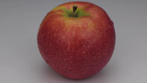 Rotation of a red apple in drops of dew on a white background Footage