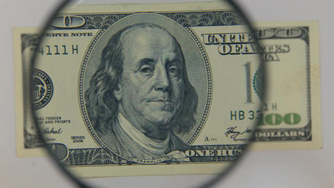 Approaching using a magnifying glass hundred dollar bill Footage