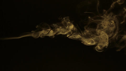 Stream of yellow smoke turning into smoke puffs on a black background Footage