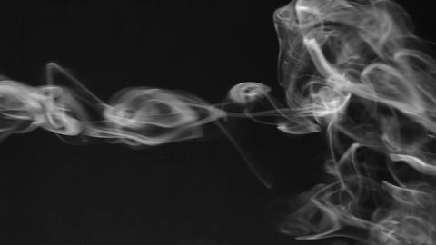 Stream of white smoke turning into smoke puffs on a black background Footage