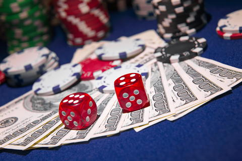 Stack of Poker chips with dice rolls on a dollar bills Photo