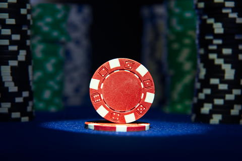 Closeup of red poker chip on blue felt card table surface with spot light on Fotografía