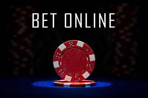 Closeup of red poker chip on blue felt card table with message BET ONLINE Photo