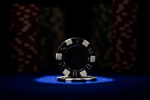 Closeup of black poker chip on blue felt card table surface with spot light on Fotografía
