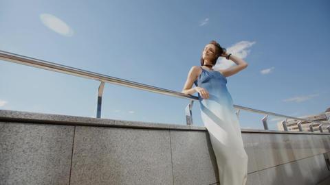 Beautiful girl in long dress posing in the wind in city street Footage