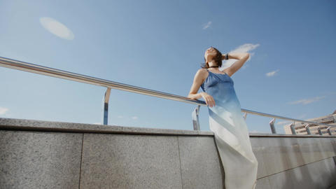 Young model in long dress posing in the wind in city street Footage