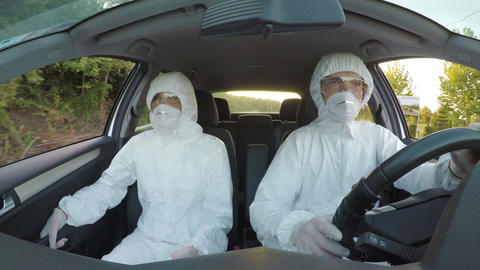 Young technician in hazmat suit talking to and arguing with his colleague in car Footage