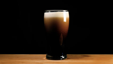 A pint of dark ale beer or stout is poured up Live Action