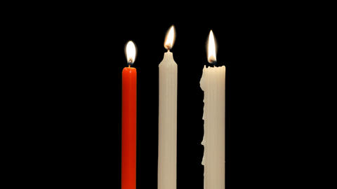 One red and two simple white candles with flickering flame, alpha channel Footage