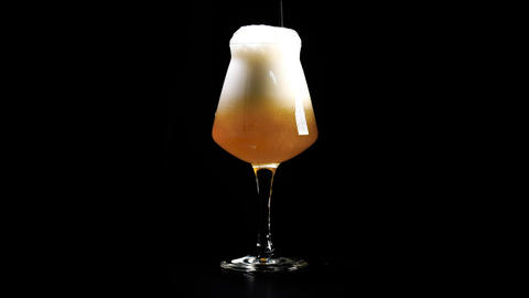 An unfiltered hand crafted beer is poured into glass against a black background Live Action