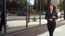 Young confident business woman goes to work with documents in hands Footage