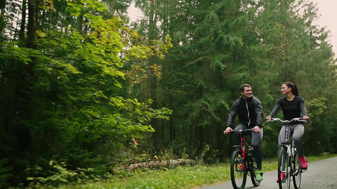 Attractive couple walking with bicycles and drinking water in the forest Footage